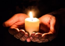 Open hands holding candles - Disaster Relief Fund